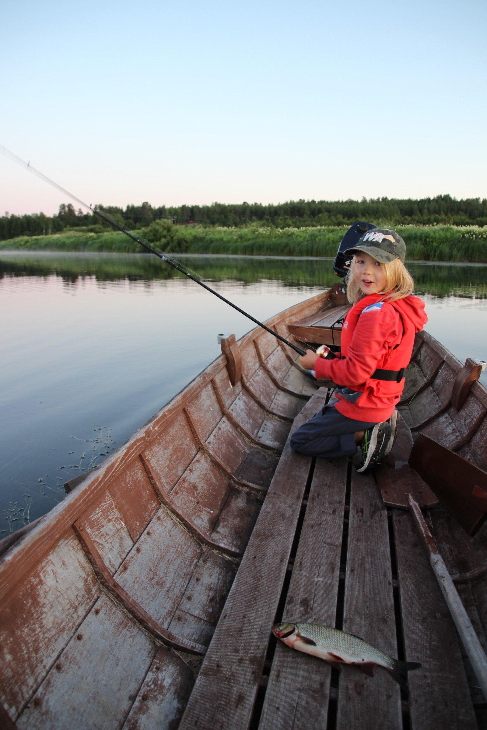 Lapsi kalastaa jokiveneestä Nivankylässä (c) Piia Juntunen-Laakso 2020